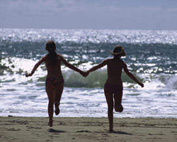 Two people running hand in hand near ocean