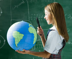 Girl holding magnifying glass looking at globe