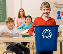 girl in classroom holding recycling bin