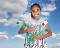 girl smiling holding recyclable bottles