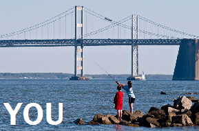 Photo for 'You': Two people fishing in a bay by a bridge.