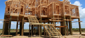 Stilts are added to the framework of a house on the beach